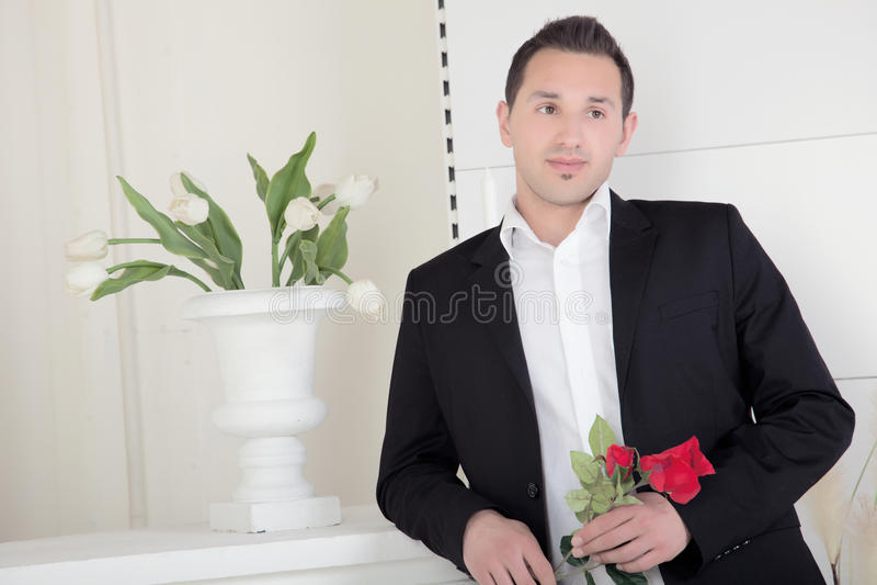 Homme romantique avec une rose rouge photographie stock