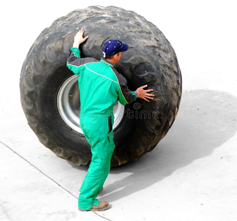 Homme roulant la roue énorme de camion photographie stock
