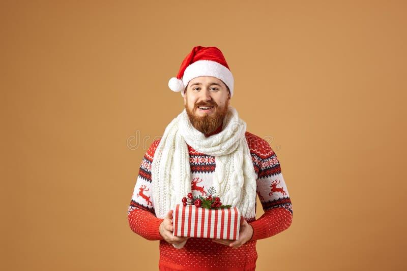 Homme roux de sourire avec la barbe habillée dans un chandail rouge et blanc avec des cerfs communs, une écharpe tricotée blanche photographie stock libre de droits
