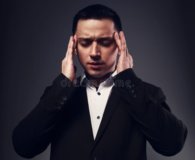 Homme sérieux avec des capacités de transfert de pensées tenant les mains la tête avec les yeux fermés en costume noir sur studio images libres de droits