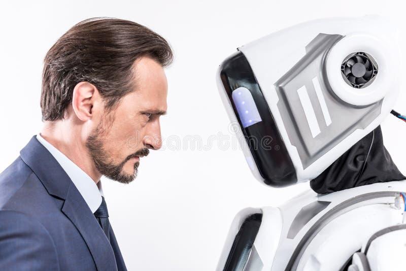 Homme sérieux ayant le contact visuel avec le cyborg photographie stock