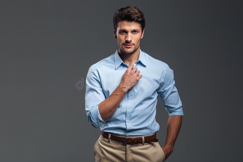 Homme sérieux bel boutonnant sa chemise d'isolement photos stock