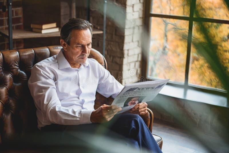 Homme sérieux concentré regardant par le journal images stock