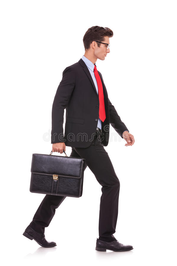 Homme sérieux d'affaires avec la serviette et la marche photographie stock libre de droits