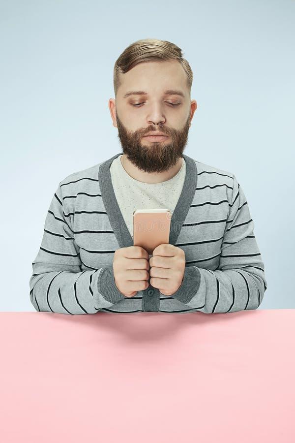 Homme sérieux d'affaires avec le téléphone portable se reposant à la table photo stock