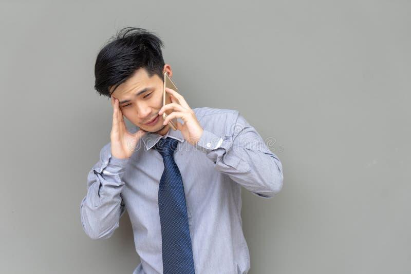 Homme sérieux d'affaires parlant au téléphone portable sur le fond gris photos stock
