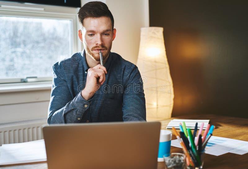 Homme sérieux d'affaires travaillant sur l'ordinateur portable photographie stock libre de droits