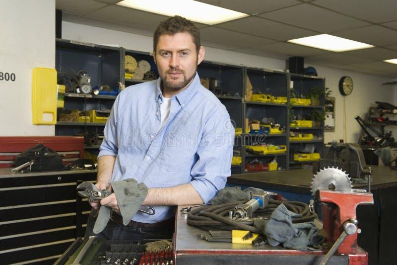 Homme sérieux dans l'atelier avec des outils image libre de droits