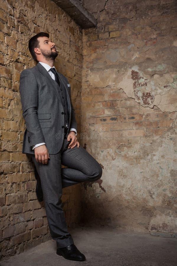 Homme sérieux dans un costume gris se tenant dans un milieu urbain photographie stock libre de droits
