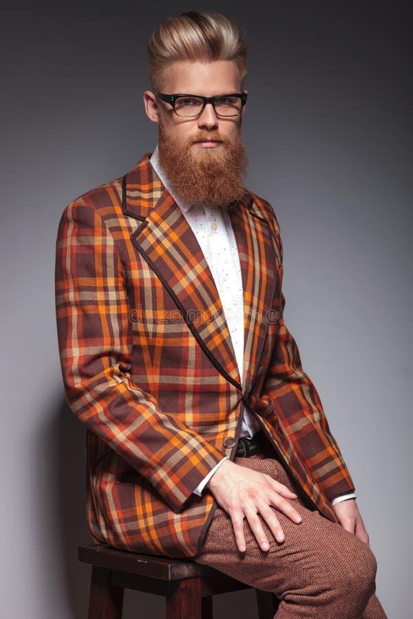 Homme sérieux de mode avec la longue séance de barbe photo stock