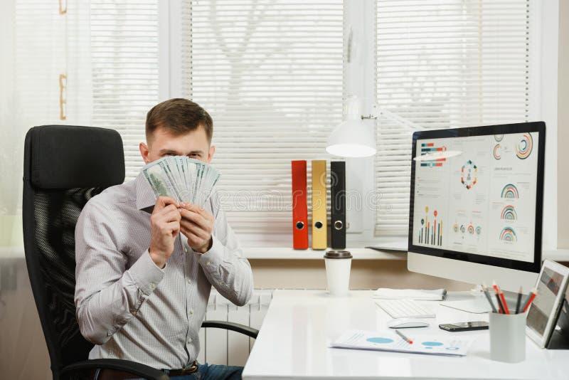 Homme sérieux et rédigé d'affaires dans la chemise se reposant au bureau, fonctionnant à l'ordinateur avec le moniteur moderne Di photo stock