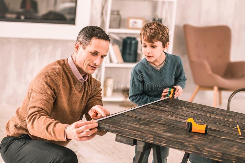 Homme sérieux occupé demandant à son fils de la préadolescence l'aide mesurant la table photos libres de droits