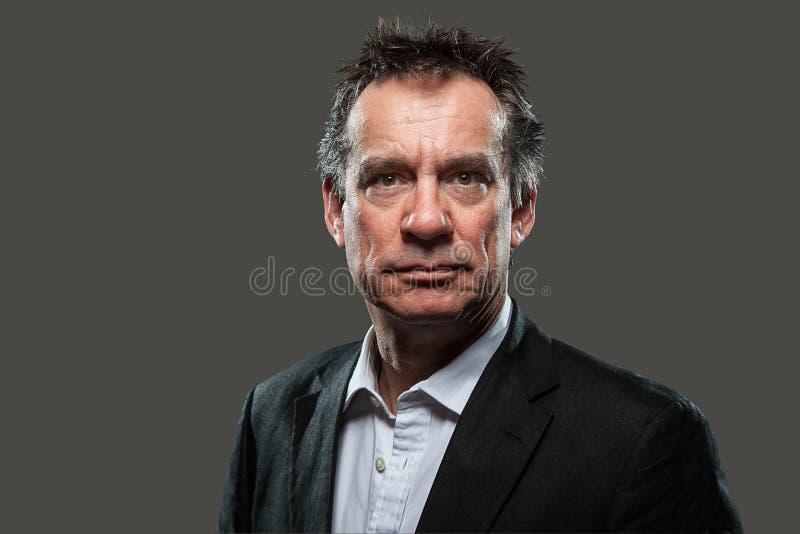 Homme sévère d'affaires dans le procès contrasté photo stock