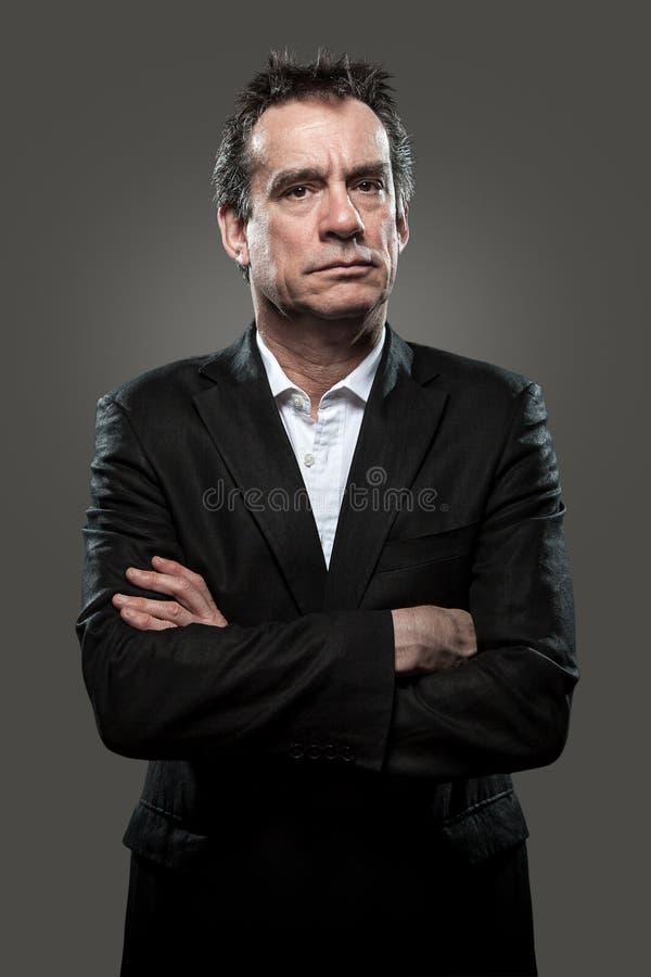 Homme sévère d'affaires dans le procès contrasté photos stock