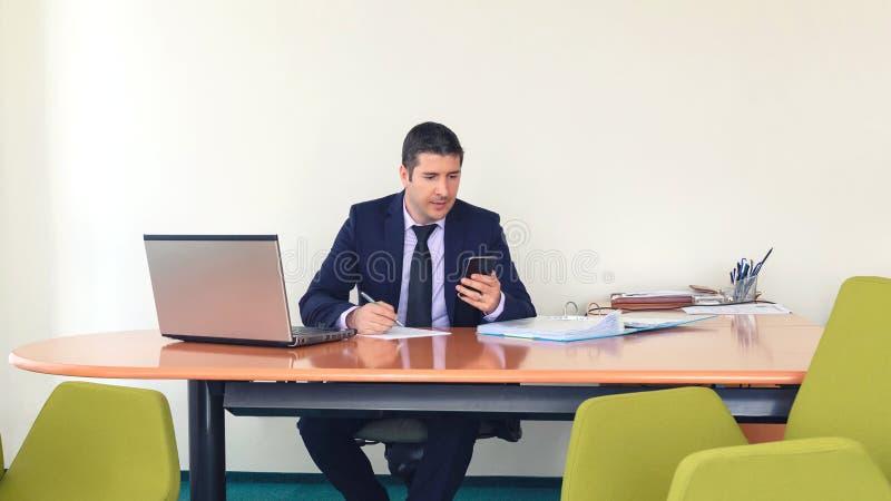 Homme sûr d'affaires dactylographiant sur le smartphone et écrivant un document tandis qu'assis au bureau dans offic photographie stock