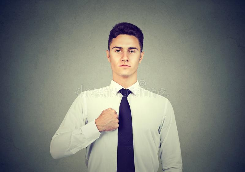 Homme sûr dans la chemise blanche d'isolement sur le fond gris photo libre de droits