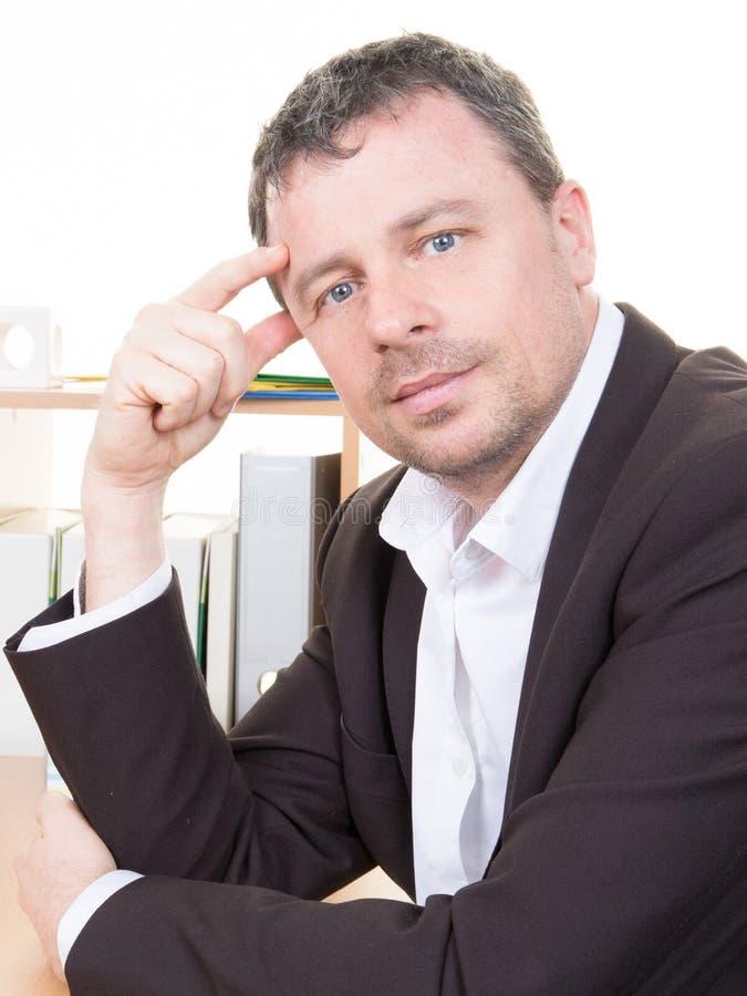 homme sûr de directeur s'asseyant au bureau et regardant l'homme d'affaires de sourire d'appareil-photo travaillant au bureau photo libre de droits