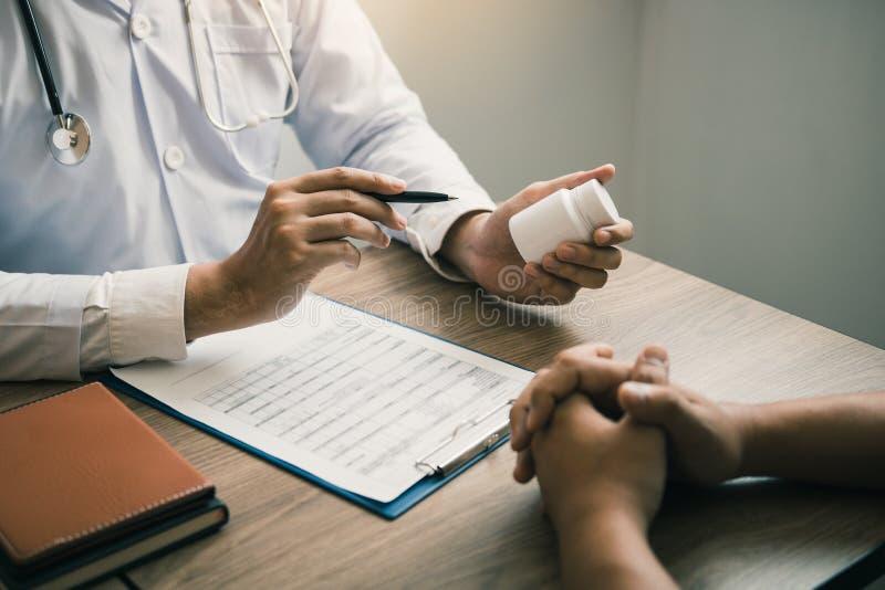 Homme sûr de docteur tenant une bouteille de pilule et parlant avec le patient supérieur et passant en revue son médicament à la  images stock