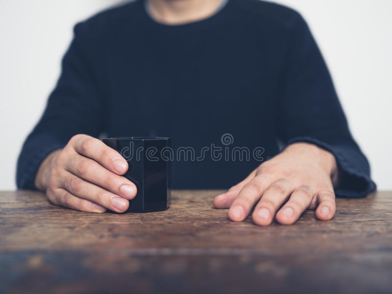 Homme s'asseyant à la table avec la tasse images stock