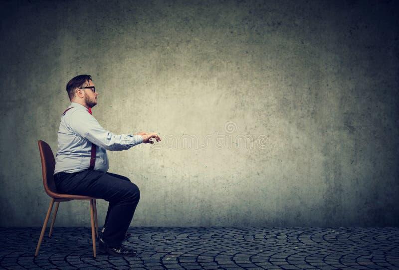 Homme s'asseyant à la table imaginaire images stock
