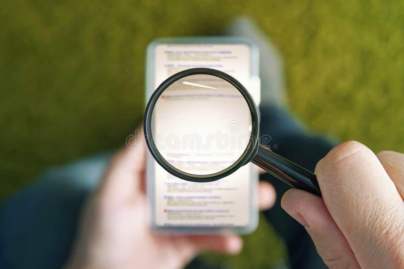 Homme s'asseyant avec la loupe transparente au-dessus de la page de moteur de recherche de lecture rapide de smartphone L'espace  image stock