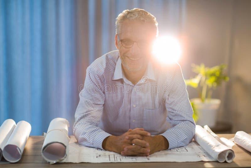 Homme s'asseyant avec le modèle à son bureau photos stock