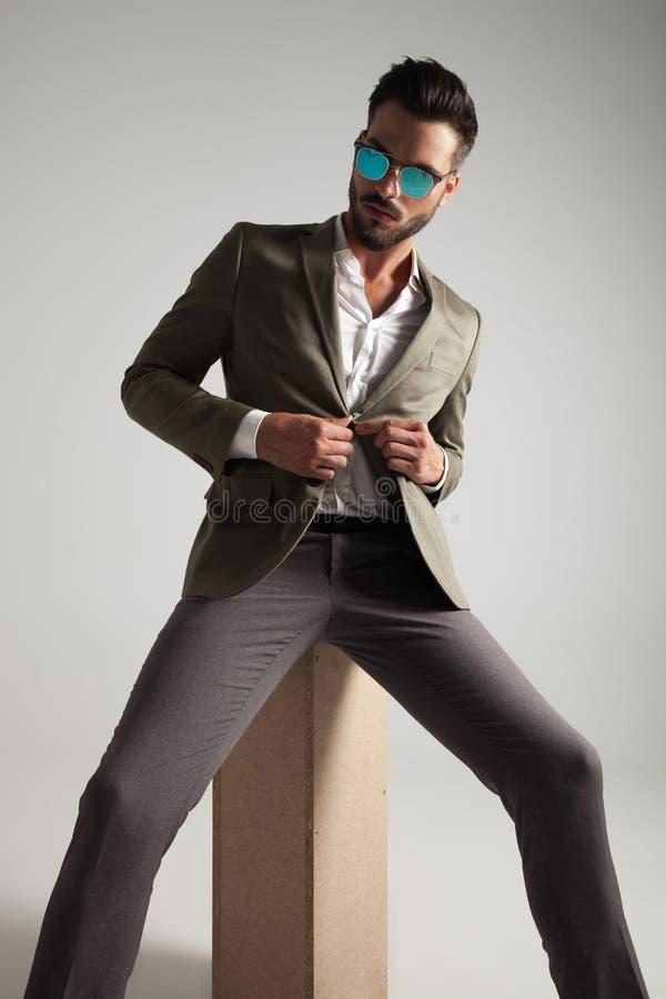 Homme s'asseyant bel avec des lunettes de soleil boutonnant son costume vert images libres de droits
