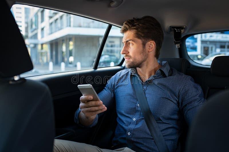 Homme s'asseyant dans la voiture utilisant le téléphone intelligent photographie stock