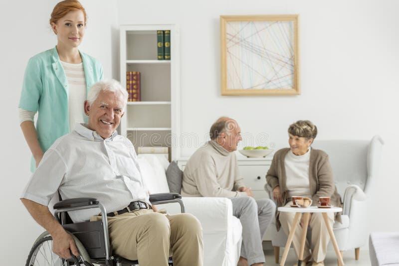 Homme s'asseyant dans le fauteuil roulant image stock