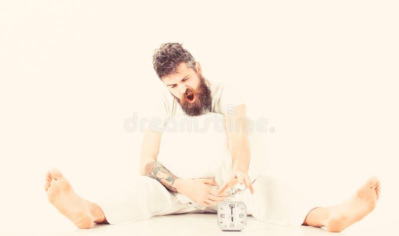 Homme s'asseyant dans le pyjama et essayer d'arrêter l'horloge image stock