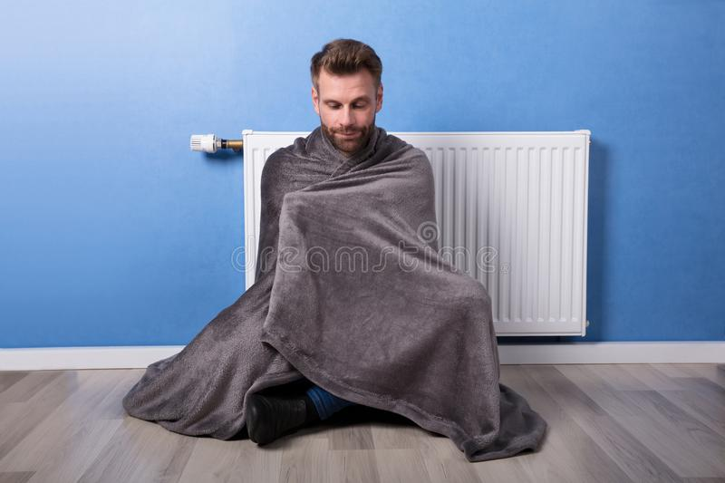 Homme s'asseyant en Front Of Heater At Home photographie stock