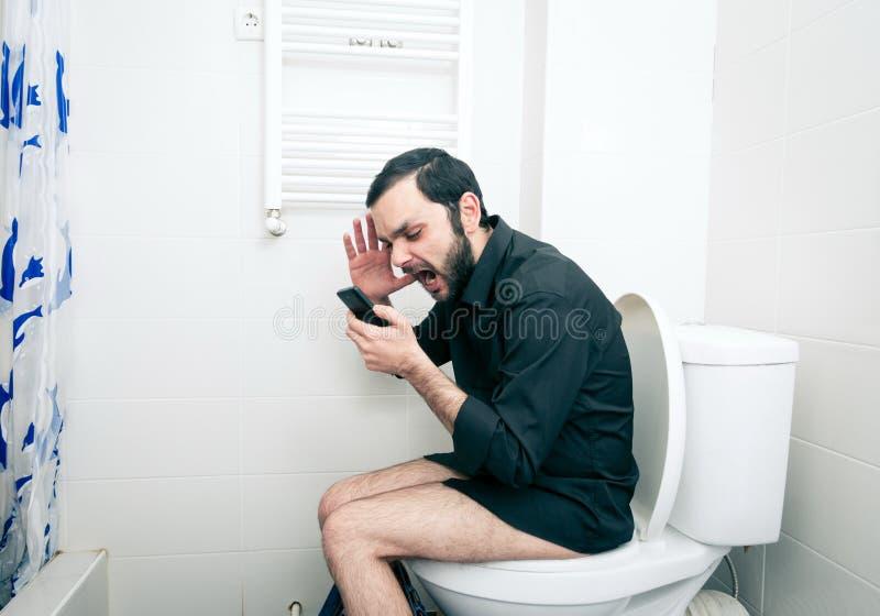 Homme s'asseyant la toilette et en parlant photo stock