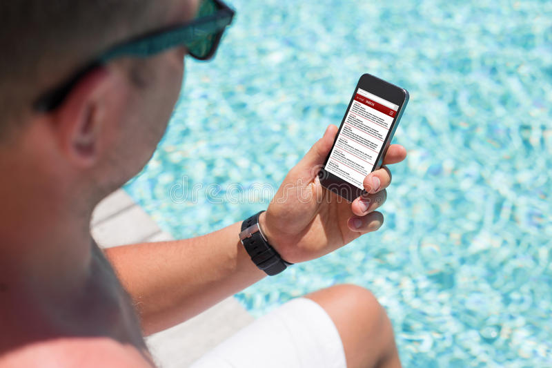 Homme s'asseyant par la piscine et vérifiant l'email sur son smartphone images libres de droits