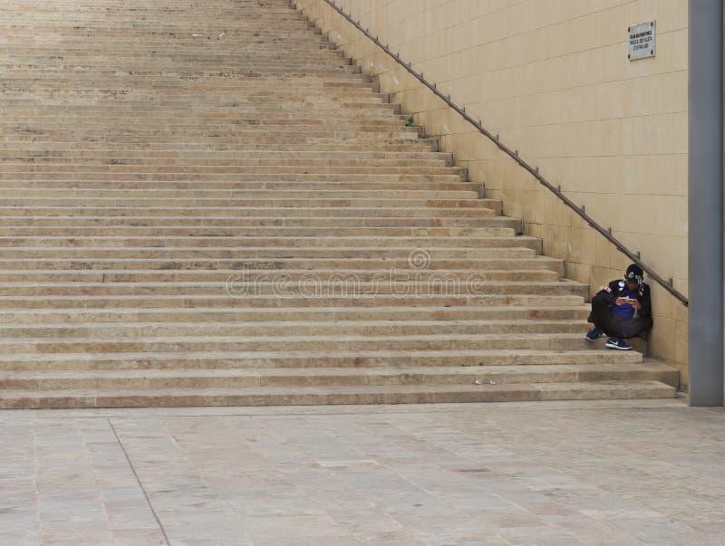 Homme s'asseyant sur des escaliers tout en jouant avec son téléphone photos stock