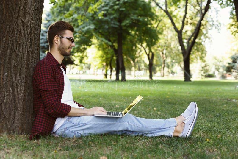 Homme s'asseyant sur l'herbe avec l'ordinateur portable dehors photographie stock libre de droits