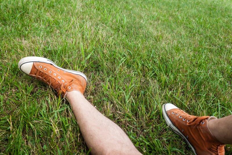 Homme s'asseyant sur l'herbe utilisant les espadrilles oranges photographie stock libre de droits