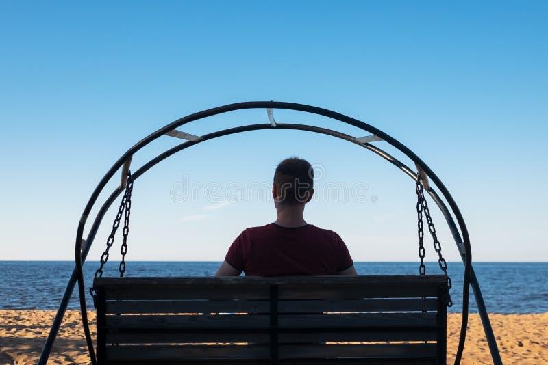 Homme s'asseyant sur l'oscillation à la plage sablonneuse et regardant sur la mer images stock