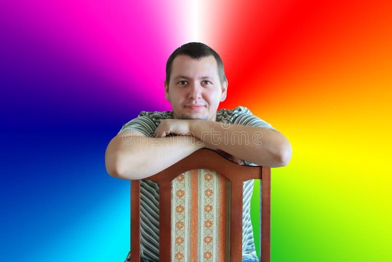 Homme s'asseyant sur la chaise sur le fond de couleurs d'arc-en-ciel photos libres de droits