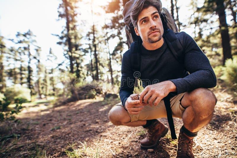 Homme s'asseyant sur la traînée de forêt utilisant un sac à dos photos stock