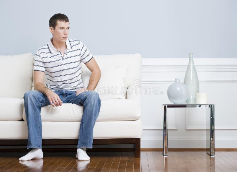Homme s'asseyant sur le divan de salle de séjour image stock