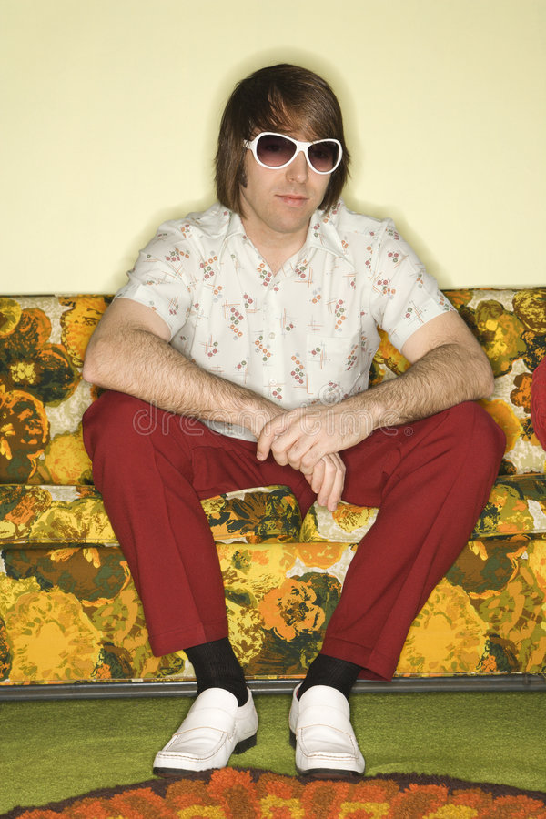 Homme s'asseyant sur le sofa. photo stock