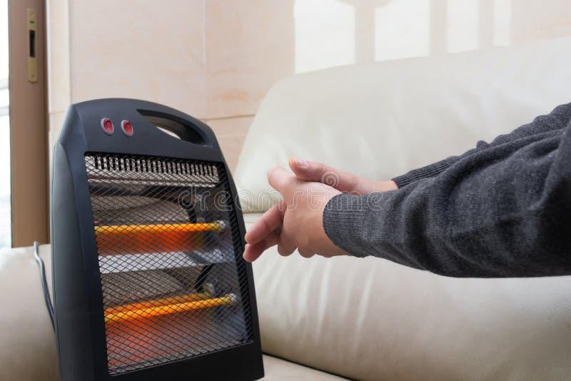 Homme s'asseyant sur le sofa avec le radiateur électrique près de ses mains photo stock