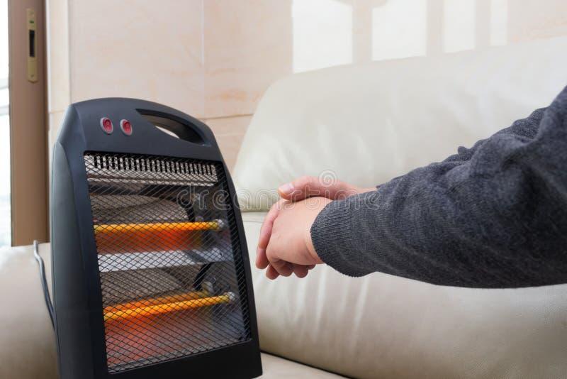 Homme s'asseyant sur le sofa avec un radiateur électrique près de ses mains photographie stock libre de droits