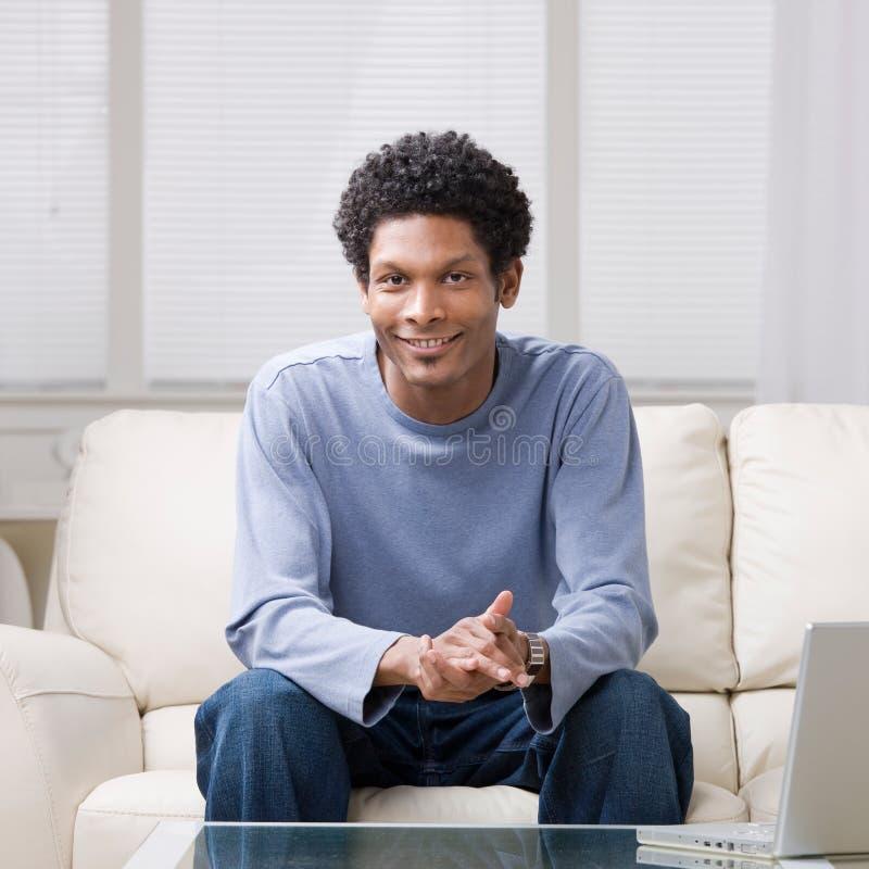 Homme s'asseyant sur le sofa dans la salle de séjour photographie stock