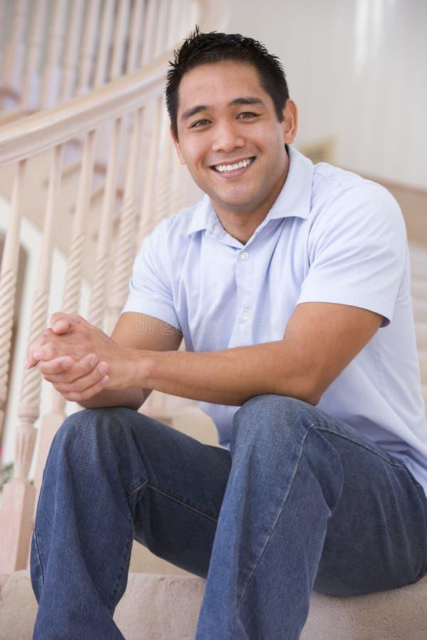 Homme s'asseyant sur le sourire d'escalier image libre de droits