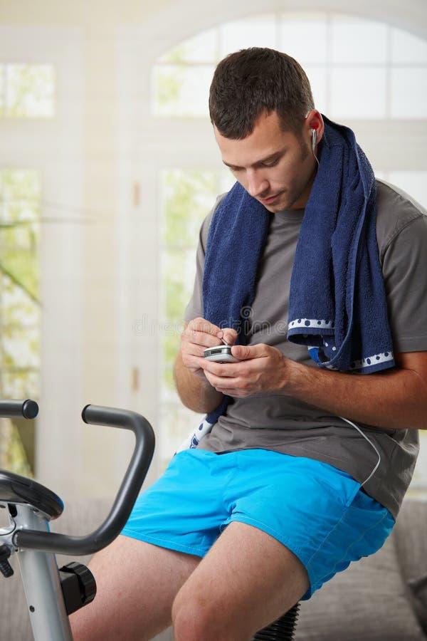 Homme s'asseyant sur le vélo stationnaire photo stock