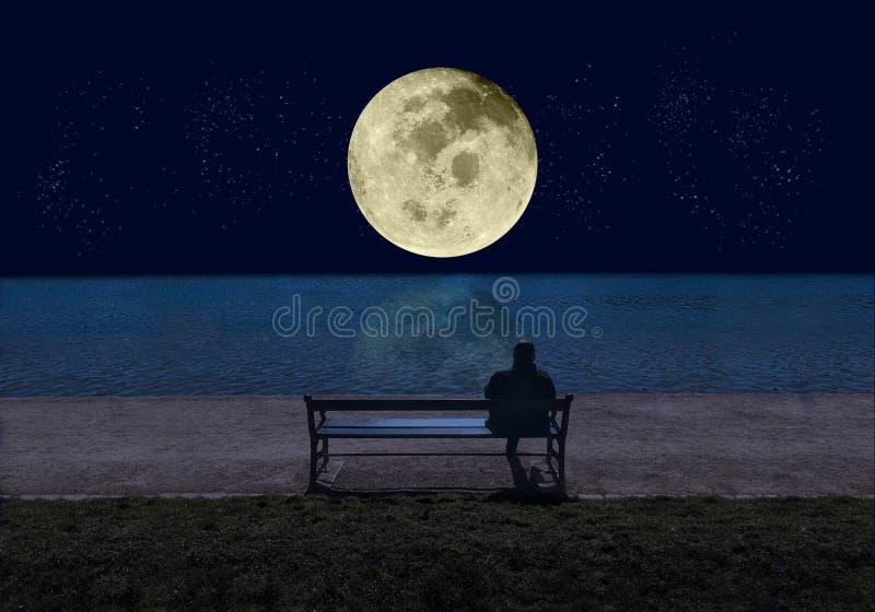 Homme s'asseyant sur un banc par la mer pendant la nuit et regardant une grande pleine lune brillante avec des ?toiles se refl?ta images libres de droits