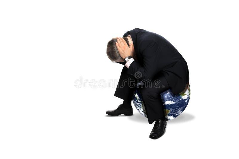 Homme s'asseyant sur un globe photographie stock
