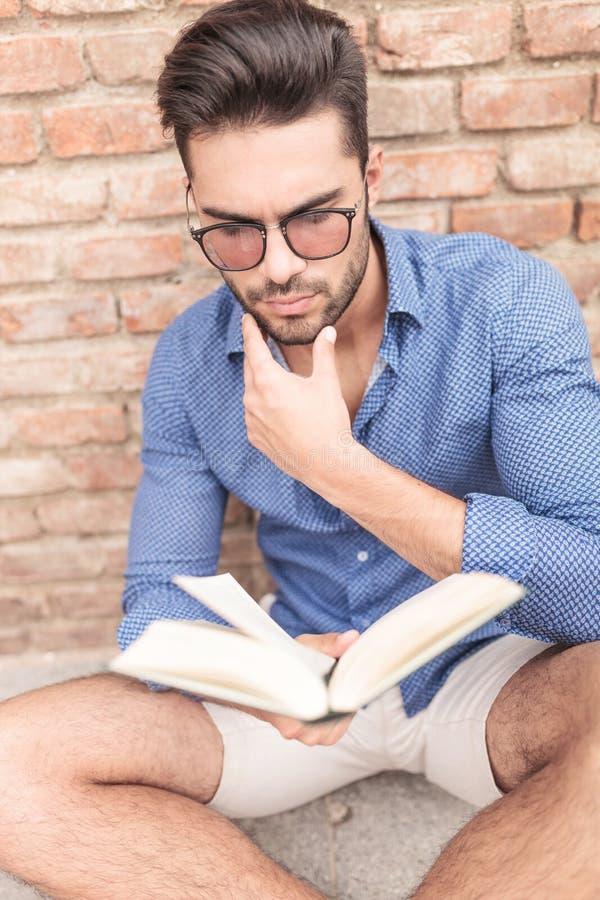 Homme s'interrogeant sur la fin du livre qu'il lit photographie stock libre de droits