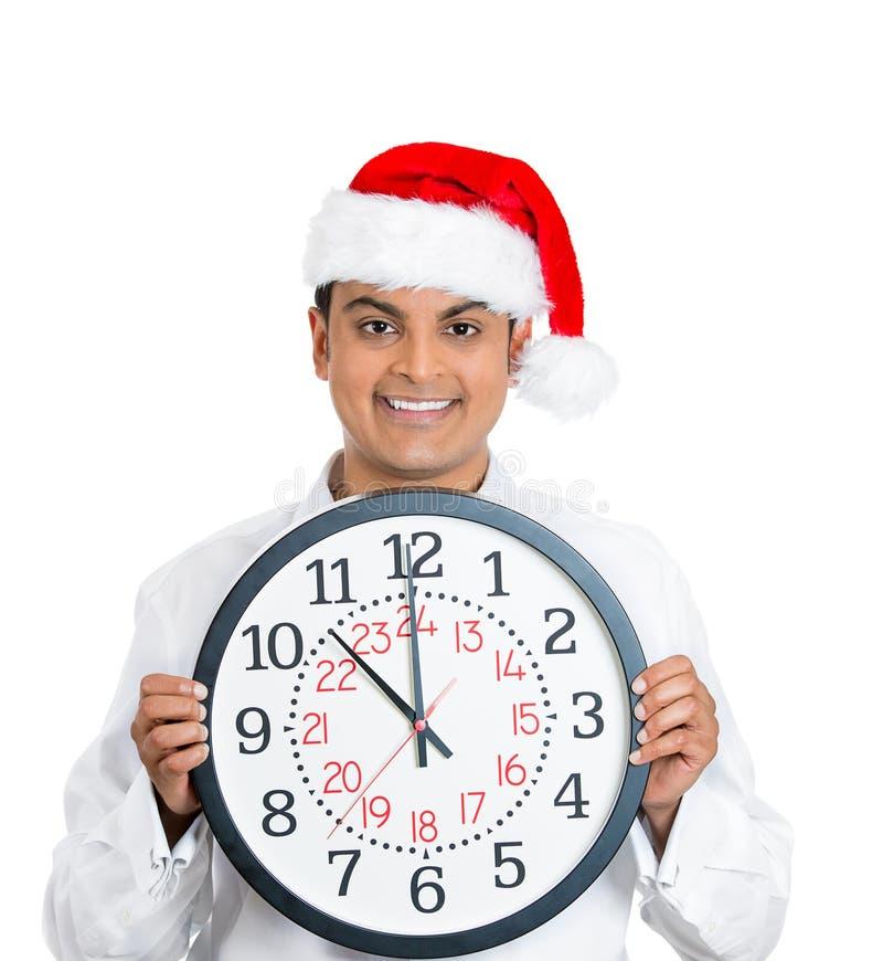 Homme sûr et futé de Noël de jeunes tenant l'horloge image stock